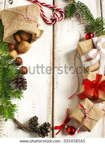 Christmas frame. Christmas fir branches, pine cones a and gifts on wooden background - stock photo