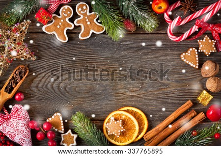 Christmas frame. Gingerbread cookies, spices and decorations on wooden background.