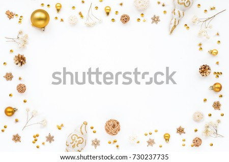Christmas frame made of white and golden christmas decorations on white background. Flat lay, top view, copy space