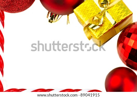 Christmas frame of red baubles and golden gift isolated on white
