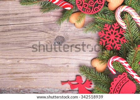 Christmas frame on a wooden texture with of Christmas trees branches and toys. - stock photo