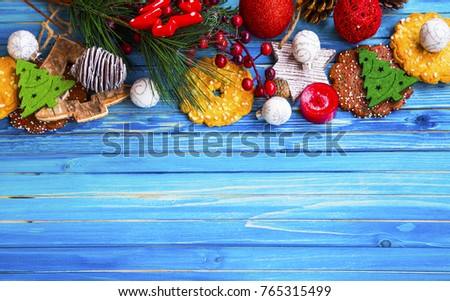 Christmas frame with festive ornaments and cookies, decorations on wooden painted boar, top view