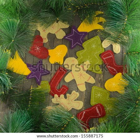 Christmas frame with funny felt figures on wooden background and conifer branches - stock photo