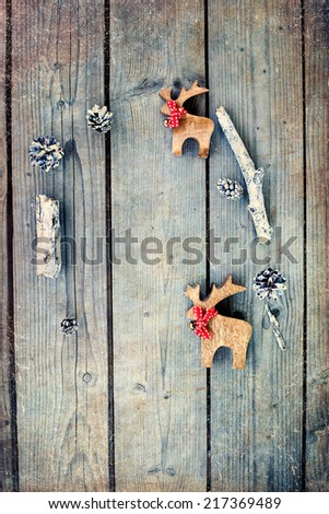 Christmas frame with wooden decorations  (cones, twigs and two reindeer) on old grunge wooden background. Vintage Christmas frame/card.  - stock photo