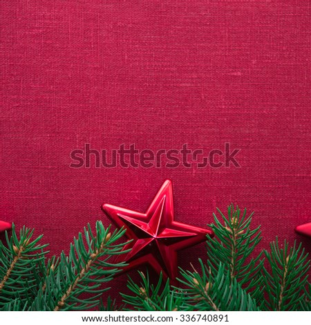 Christmas frame with xmas tree and ornaments on red canvas background. Merry christmas card. Winter holidays. Xmas theme. Space for text. Happy New Year. - stock photo