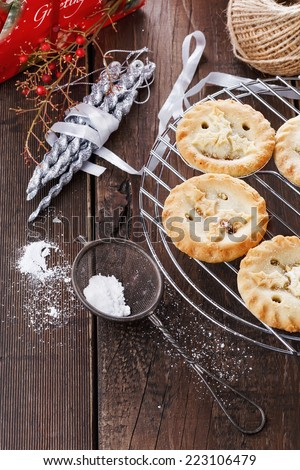 Christmas fruit mince pies and Christmas ornaments over rustic wooden background - stock photo