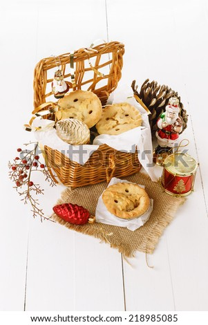 Christmas fruit mince pies in a woven basket and Christmas decorations over white wooden background - stock photo