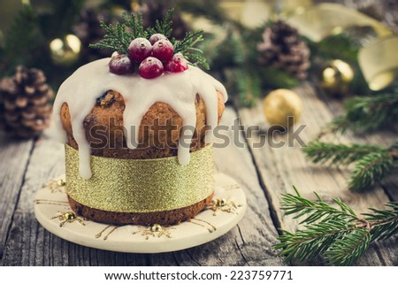 Christmas fruitcake decorated with icing and berries, toned - stock photo