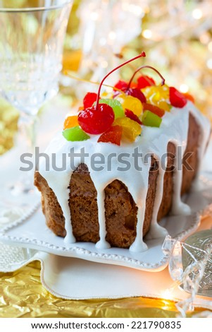 Christmas fruitcake with sugar icing and candied fruits - stock photo