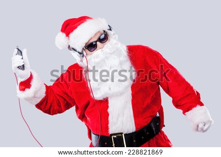 Christmas fun. Santa Claus in sunglasses and headphones listening to MP3 Player and dancing while standing against grey background - stock photo