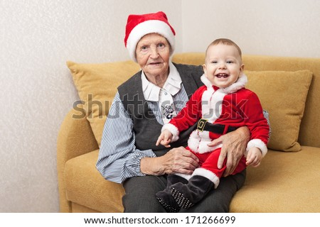 Christmas funny small baby in Santa Claus clothes with his grandmother  - stock photo