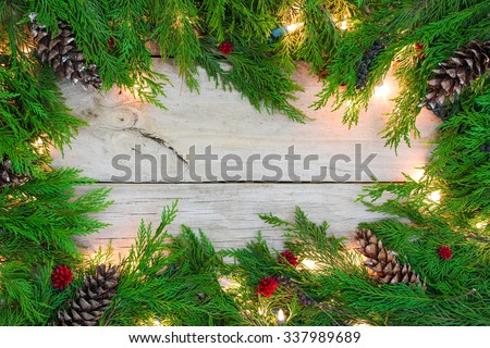 Christmas garland border with lights, pine cones and berries on antique rustic wooden background - stock photo