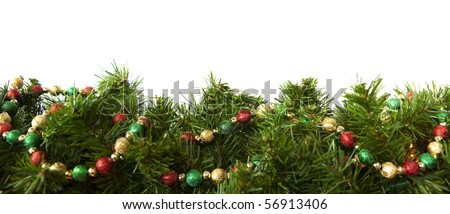 Christmas garland decorated with a string of festive baubles, over white background. - stock photo