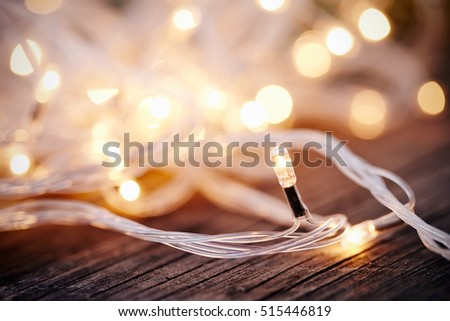 Christmas garland lights from LED bulbs on the wooden background