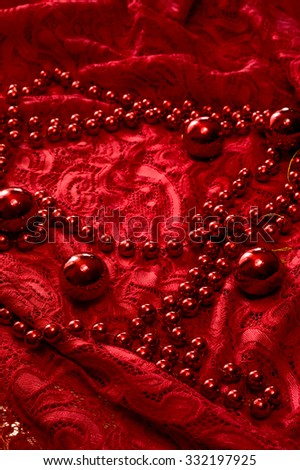 Christmas garland made from small red beads.On A Red Background. New year toy. Toned - stock photo