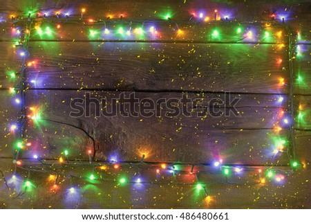 Christmas garland with colored paws on a dark wooden background with the processing of small yellow dots and yellow glow.