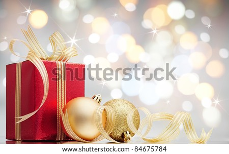 christmas gift and baubles against bokeh lights background