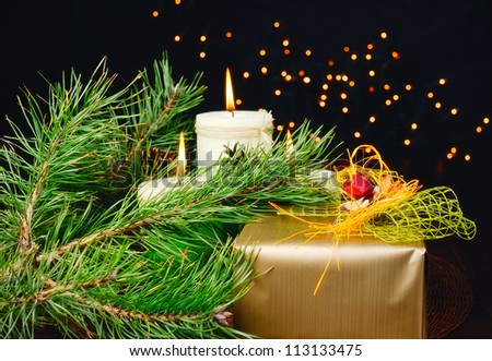 Christmas gift and candle on black background of defocused golden lights. - stock photo