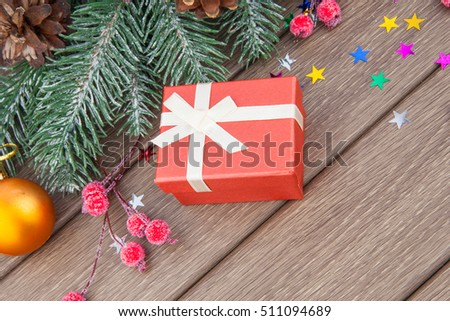 Christmas gift and decoration in red color on wooden background