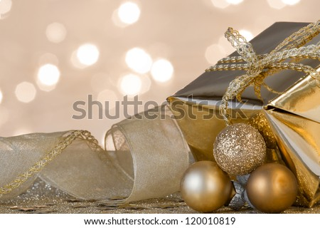 Christmas gift and decorations on defocused lights background in gold, with focus on ribbons and bow