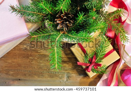 Christmas gift and package items (fir branches in basket, boxes, ribbons) with copy space. Top view