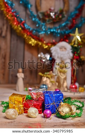 Christmas gift and Santa claus dall, Christmas decoration. Decoration of X'mas and New Year Celebration. Selective focus on a gift. - stock photo