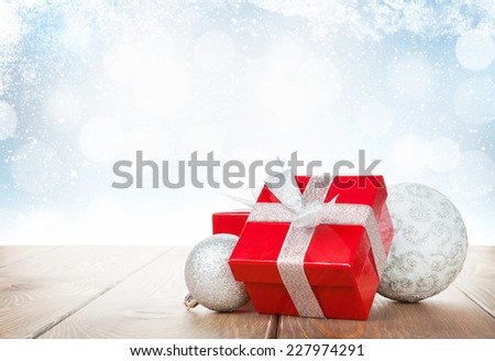 Christmas gift box and baubles on wooden table with snow bokeh background for copy space - stock photo