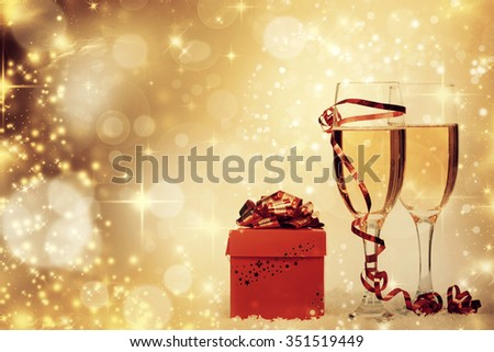 Christmas gift box and champagne on sparkling background - stock photo