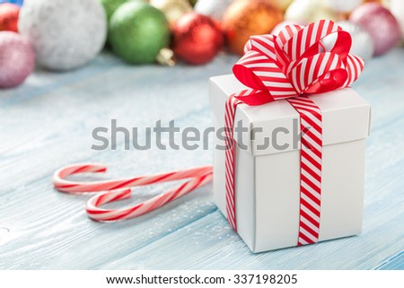 Christmas gift box and colorful baubles decor on wooden table - stock photo