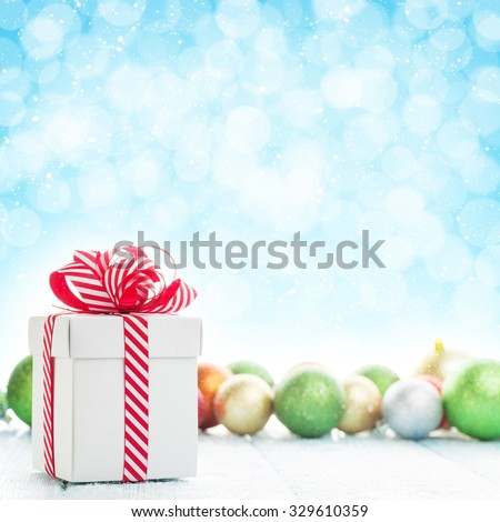 Christmas gift box and colorful baubles decor on wooden table with bokeh background for copy space - stock photo