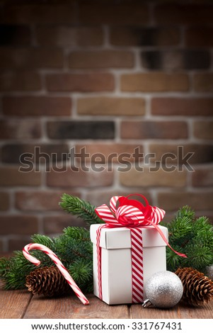 Christmas gift box and fir tree branch on wooden table. View with copy space - stock photo