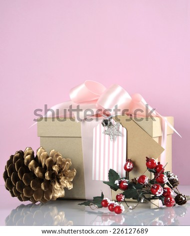Christmas gift box in modern trend natural gift wrapping with brown kraft paper boxes and pale pink ribbon, pine cone and berries decorations. Vertical with copy space. - stock photo