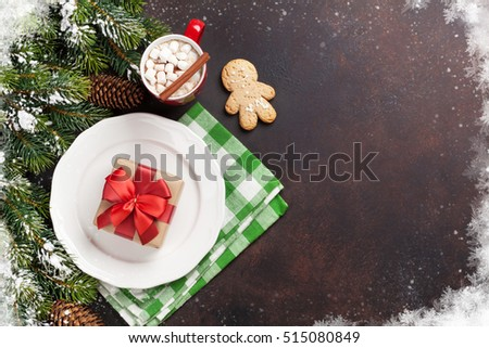 Christmas gift box on plate, hot chocolate with marshmallow and fir tree. Top view with copy space