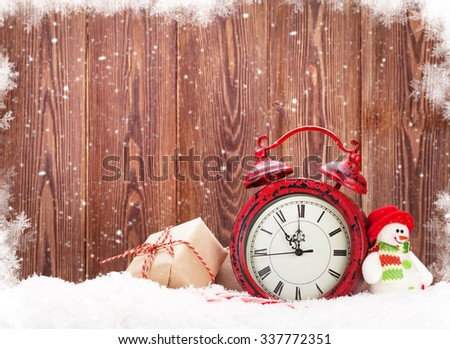 Christmas gift box, snowman toy and alarm clock in snow. View with copy space - stock photo