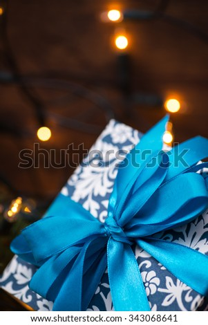 Christmas gift box with blue bow and bokeh lights on a fir-tree branch