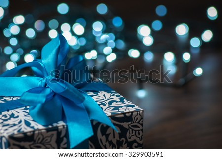 Christmas gift box with blue bow and bokeh lights on wooden surface - stock photo