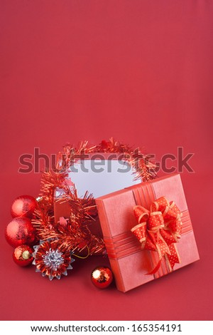 Christmas gift box with decorations and color ball  on red background