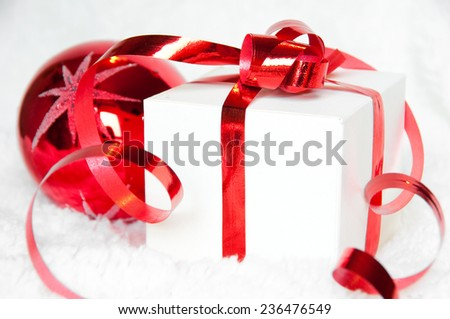 Christmas gift box with red ribbon and a ball - stock photo