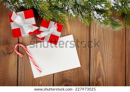 Christmas gift boxes and blank greeting card over wooden background with snow fir tree - stock photo