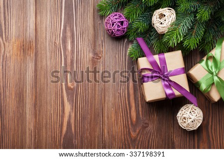 Christmas gift boxes and fir tree on wooden table. Top view with copy space - stock photo