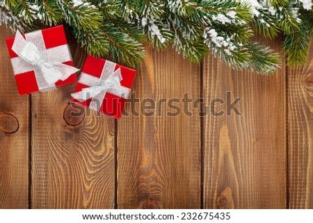 Christmas gift boxes and snow fir tree over wooden background with copy space - stock photo