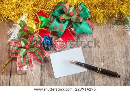 Christmas gift boxes and white note over wooden background