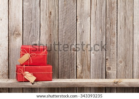 Christmas gift boxes in front of wooden wall. View with copy space - stock photo
