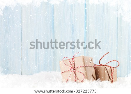 Christmas gift boxes in snow and wooden background with copy space - stock photo