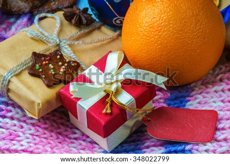 Christmas gift boxes, orange, cookie and winter scarf - stock photo