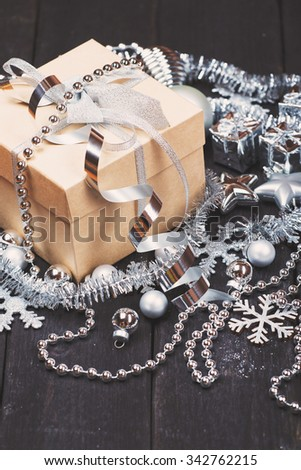 Christmas gift boxes with silver Christmas decoration on wooden background