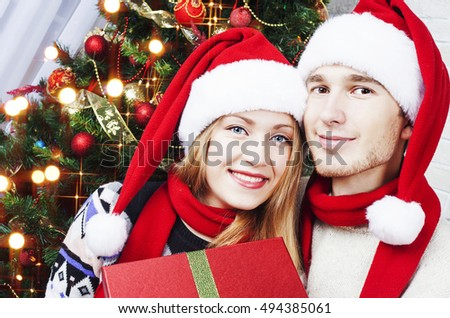 Christmas Gift. Happy Couple in Santa's Hat with Christmas and New Year Gift at Home.