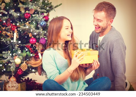 Christmas Gift. Happy Couple with Christmas and New Year Gift at Home. Smiling Family Together. Christmas tree  - stock photo