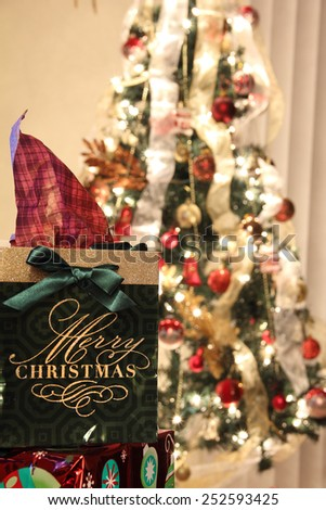 Christmas gift in front of a christmas tree with lights - stock photo