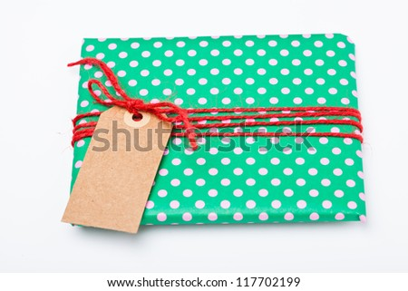 Christmas gift in green wrapping with dots, red string and brown cardboard tag - stock photo